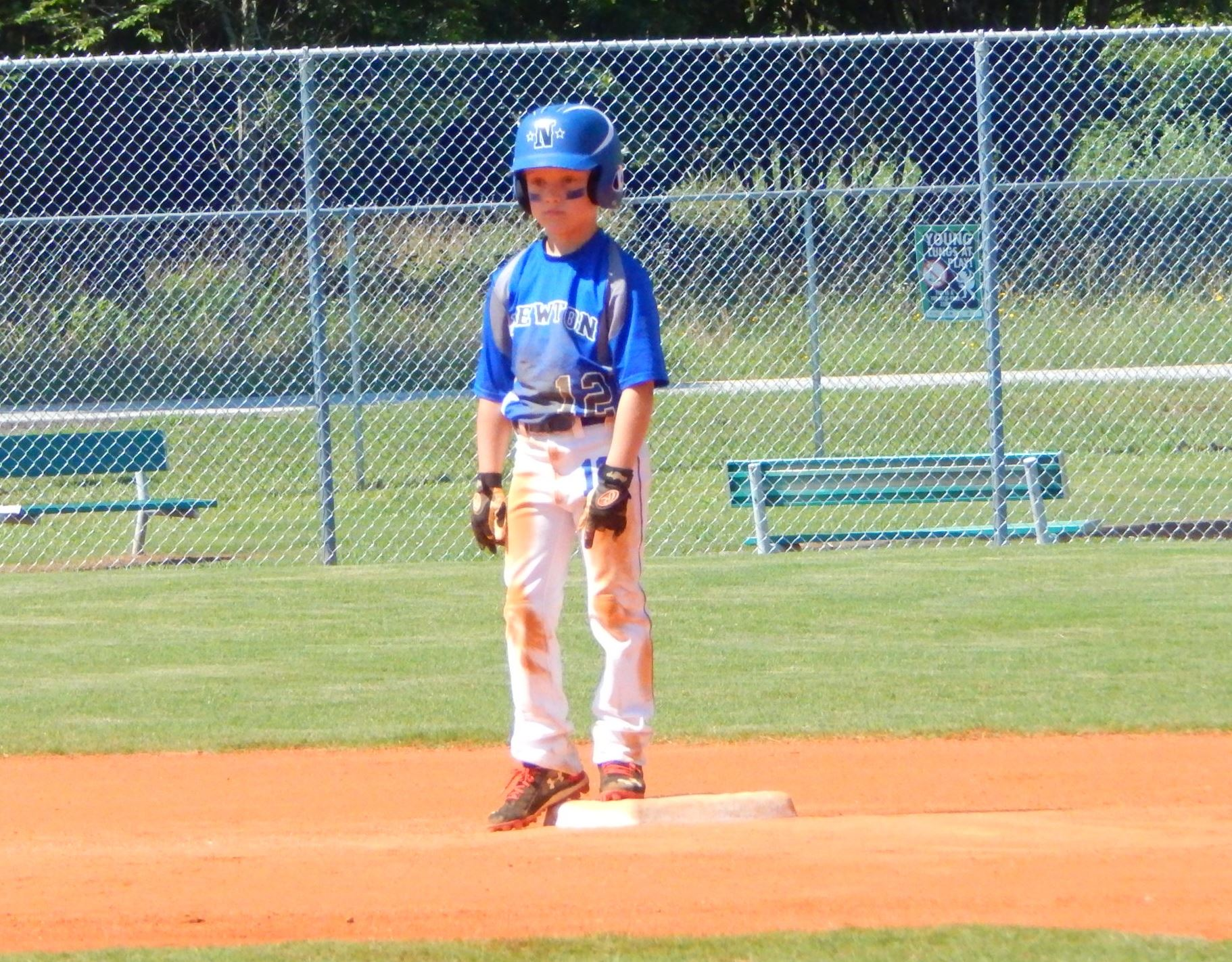 Young baseball player standing on a base